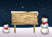 Cute Snowmen with a blank wooden sign — Stock Photo