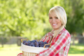 A Blonde Woman Holding a Basket of Plums — Stock Photo