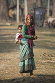 Old nepali woman carrying a young boy — Stock Photo