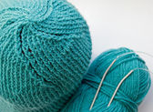 Turquoise knitted hat and wool ball with knitting needles — Stock Photo