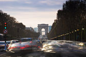 Triumphal Arch and Champ Elysses in Paris with moving cars — Stock Photo