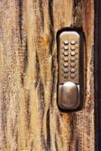 PIN keypad with numbers and letters carved in the wooden door — Stock Photo