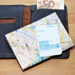 Traveling concept composition with wallet, money, map and a airplane boarding pass — Stock Photo