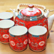 Stock Photo: Red set of teapot and tecups on wooden table