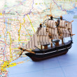Travel concept. A globe and a toy ship on a USA east coast map background — Stock Photo