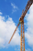 Yellow tower crane on a beautiful blue sky background — Стоковое фото