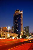 Red road contrasts with blue sky in this Abu Dhabi streetscape — Stock Photo