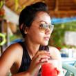 giovane donna in un top nero e occhiali da sole sorseggiando un drink in un ristorante sulla spiaggia in Thailandia in una giornata di sole estivo — Foto Stock