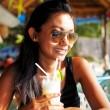 jeune femme dans un haut noir et des lunettes de soleil boire un verre dans un restaurant de plage en Thaïlande sur une journée d'été ensoleillée — Photo #25354649