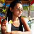 Young woman in a black top and sunglasses enjoying a drink in a beach restaurant in Thailand on a sunny summer day — Stok fotoğraf