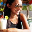 mujer joven en un top negro y gafas de sol disfrutando de una copa en un restaurante de playa en Tailandia en un día soleado de verano — Foto de Stock