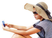 Young woman in a hat and sunglasses using her mobile phone — Stock Photo