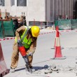 A laborer uses a jackhammer to break up a concrete pavement — Stock Photo #38296791