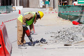 A laborer uses a jackhammer to break up a concrete pavement — Stock Photo