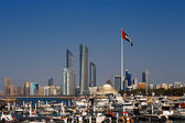 A skyline view of the Abu Dhabi including the UAE National Flag — Stock Photo