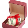 Dollars laying in red decorated gift box, isolated on a white — Stock Photo