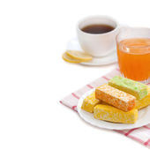 Multi-colored candy, tea with lemon, apricot juice on a white background — Stock Photo