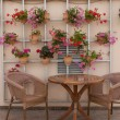 Wicker chairs and a table on the terrace with flowers — Stock Photo