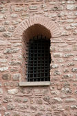 Medieval castle - details of a window with iron grating — Stock Photo