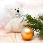 Spielzeug-eisbär und eine orange kugel auf dem weihnachtsbaum — Stockfoto