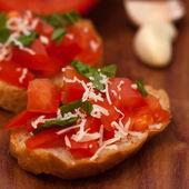 Bruschetta com ciabatta grelhado, azeite, tomate picado, alho e Salsa folhas na placa de madeira — Fotografia Stock