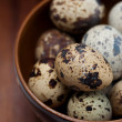 Quail eggs in a wooden bowl on a wooden background — Stock Photo