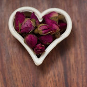 Heart made of dried rose buds — Stock Photo
