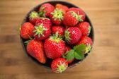 Färska jordgubbar i en trä skål på en trä bakgrund — Stockfoto