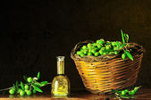 Green olives with bottle of olive oil — Stock Photo