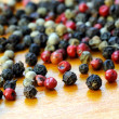 Black white and pink peppercorns on wood — Stock Photo