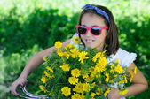 Little Girl with bike and daisies — Stock Photo