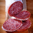 Seasoned salami on chopping board — Stock Photo
