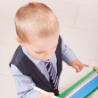 Suit up small young boy working on the chalkboard — Stock Photo