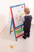 Ponte el traje pequeño muchacho trabajando en el pizarrón — Foto de Stock