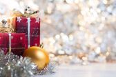 Christmas ball and gifts on abstract light background — Stock Photo