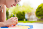 Girl with brush painting an art image — Stock Photo