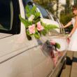 Bride is standing by limousine car — Stock Photo
