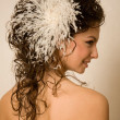 Feather hairpin in curly hair — Stock Photo