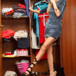 Beautiful young woman stands near her wardrobe in different sho — ストック写真