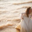 Bride in lace dress is standing near waterline - Stock Photo