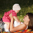 Stock Photo: Young woman with her little 1 year old daughter are having fun in the park