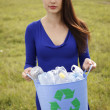 Young woman holding a blue recycling bin with plastic bottles — ストック写真