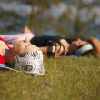 Foto Stock: Yoga group practicing outdoors