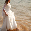 Bride in lace dress is standing near waterline — Foto Stock