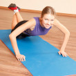 Young beautiful woman is exercising at gym — Stock Photo
