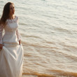 Bride in lace dress is standing near waterline — Photo
