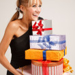 Stock Photo: Cheerful young woman with heap of gifts