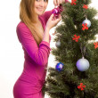Beautiful girl decorating christmas tree — Stock Photo