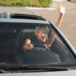 Stylish girl in car is waving her hand — Stock Photo #14177464