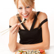Young woman eating sushi with chopsticks — Stock Photo #14177528